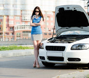Woman with the arms crossed near the broken car Royalty Free Stock Images
