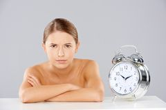 Woman with Arms Crossed Next to Alarm Clock Stock Image