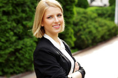 Woman with arms folded in park Royalty Free Stock Image