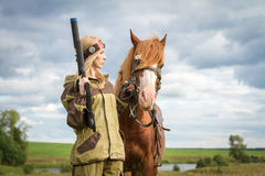 Woman with arms and a horse. A woman standing on a nature background with a horse and holding a weapon Royalty Free Stock Images