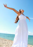 Woman with arms open enjoying her freedom. Woman relaxing at the beach with arms open enjoying her freedom wear long white dress Royalty Free Stock Photos