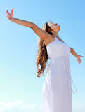 Woman with arms open enjoying her freedom. Woman relaxing at the beach with arms open enjoying her freedom wear long white dress Royalty Free Stock Images
