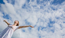 Woman with arms outstretched against blue sky and clouds Royalty Free Stock Photo