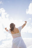 Woman with arms outstretched against blue sky and clouds Stock Photography