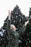 Woman with arms outstretched feeling the snow Royalty Free Stock Photography
