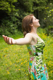 Woman with arms outstretched in field Royalty Free Stock Photos