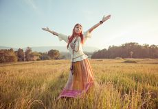 Woman with arms outstretched. Hippie woman with arms outstretched in golden field on sunset Stock Images