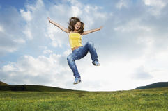 Woman With Arms Outstretched Screaming While Jumping In Park Stock Photo