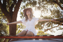 Woman with arms outstretched sitting on van Stock Photo