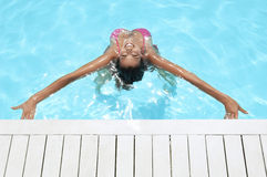 Woman With Arms Outstretched Smiling In Swimming Pool stock image