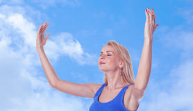 Woman with arms raised and closed eyes. Pretty young woman with arms raised and closed eyes standing on sky background Stock Photo