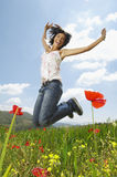 Woman With Arms Raised Jumping In Poppy Field Stock Photo