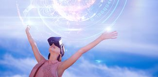Composite image of woman with arms raised looking through virtual reality simulator against white ba Royalty Free Stock Photo