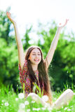 Woman with arms raised in meadow Stock Image