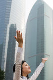 Woman with arms raised near skyscrapers Royalty Free Stock Photo