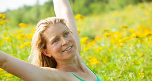 Woman arms stretched high in meadow of yellow flowers Stock Images
