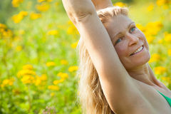 Woman arms stretched high in meadow of yellow flowers Royalty Free Stock Image