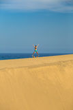 Woman with arms up outstretched jumping on sand desert dunes Stock Images