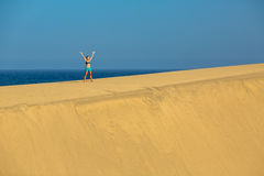 Woman with arms up raised on sand desert dunes Stock Photography