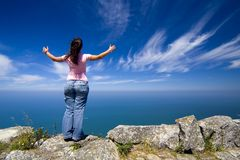 Woman with arms wide open. Young woman with arms wide open contemplating the ocean Stock Photo