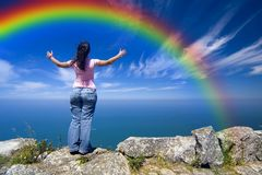 Woman with arms wide open. Young woman with arms wide open contemplating the ocean and the rainbow Royalty Free Stock Photography