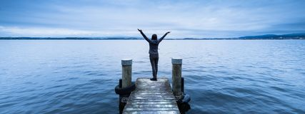 Woman with arms wide open. Wooden pier. Lake to the horizon Stock Photos