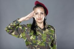 Woman army soldier saluting. Isolated on gray background Stock Images