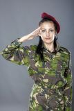 Woman army soldier saluting. Isolated on gray background Royalty Free Stock Photography