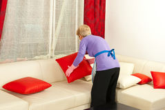 Woman arrange pillows on sofa. Back of senior woman arrange pillows on sofa home Stock Photo