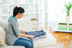Woman arrange shirts in living room Stock Photography