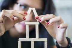 Woman arrange wooden blocks shaped a house. Young woman arrange wooden blocks shaped a house. Dream house concept stock photo
