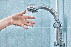 Woman arranged her hand in stream of water from shower. Female hand under the stream of water from the shower head, fixed in the holder, checks the water Stock Photos