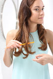 Woman arranges her hair, combing, brushing. Woman brushing her hair, arranged curls, sprayed lacquer Stock Image