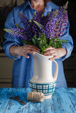 Woman arranges spring flower bouquet in a vase Royalty Free Stock Photos