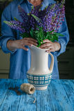 Woman arranges spring flower bouquet in a vase Royalty Free Stock Photo