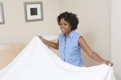 Woman Arranging Bed At Home Stock Photos