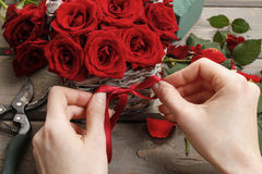 Woman arranging bouquet of red roses Royalty Free Stock Photography