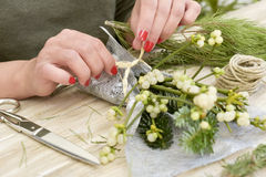 Woman arranging a bunch of mistletoe Royalty Free Stock Image