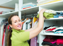 Woman arranging clothes at wardrobe. Orderly happy woman arranging clothes at wardrobe indoor Royalty Free Stock Images