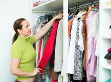 Woman arranging clothes at wardrobe. Orderly woman arranging clothes at wardrobe indoor royalty free stock images