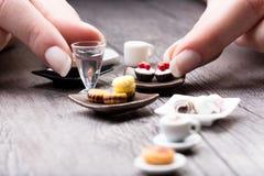 Woman arranging a miniature tea set and cookies Stock Photo