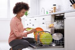 Free Woman Arranging Plates In Dishwasher Royalty Free Stock Photos - 149382618