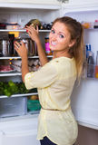Woman arranging products on fridge Stock Images