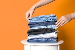 Woman arranging stack of different jeans. On table against color background stock images