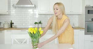 Woman arranging vase with flowers on table stock footage