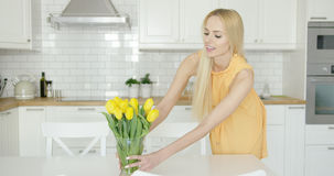 Woman arranging vase with flowers on table Stock Photo
