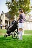 Woman arranging your golf equipment. Satisfied woman arranging your golf equipment after golf course Royalty Free Stock Image