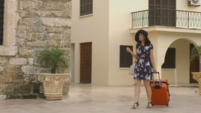 Woman arrives in beautiful city on vacation, looking around with smile on face. Stock footage stock video footage