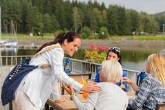 Woman arriving outdoor restaurant terrace friends. Woman arriving at outdoor restaurant terrace to her girl friends Royalty Free Stock Photo