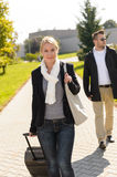 Woman arriving in park with baggage man Royalty Free Stock Image